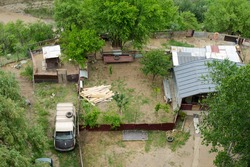 The well-established, old-times courtyard with the cabin, van, yard with assorted greenery, miscellaneous lumber items. Overhead shot in Tbilisi, Georgia. Housing and environment.