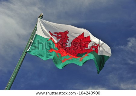 The Welsh flag against a blue sky. Motion blur at the tip of the flag. Space for text in the sky.