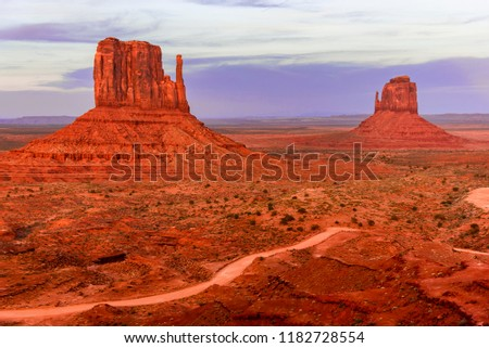 The West Mitten and the East Mitten Buttes in the evening light and a rough road line with alpine bushes along the ground besides. The Monument Valley, Navajo reservation areas, Arizona and Utah #1182728554