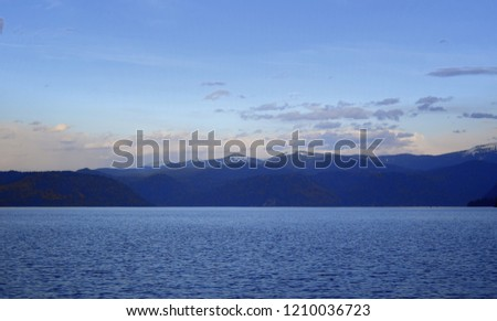 The western shore of Lake Teletsky is set at sunset, the setting sun tingles white cumulus clouds orange. The picture was taken on an autumn evening, with natural light.  #1210036723