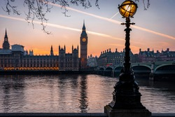 The Westminster Palace and Big Ben Tower in London, United Kingdom, during a calm sunset with street light and orange sky