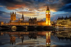 The Westminster Palace and the Big Ben clocktower by the Thames river in London, United Kingdom, just after sunset