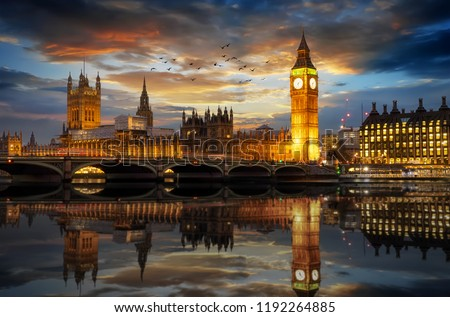 The Westminster Palace and the Big Ben clocktower by the Thames river in London, United Kingdom, just after sunset #1192264885