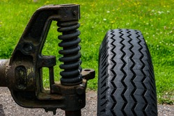 The wheel and shock absorber of a cannon from the Second World War, close-up, stands on an asphalt road against the backdrop of a lawn with green grass.