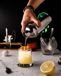 The whiskey-sour cocktail is pouring from the shaker with background of ingredients and instruments.