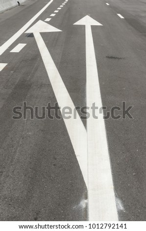 The white arrow symbol on an asphalt road, indicating direction of traffic o turn left or turn right. For the symbol concept on the street, transportation concept, change concept. Zdjęcia stock ©