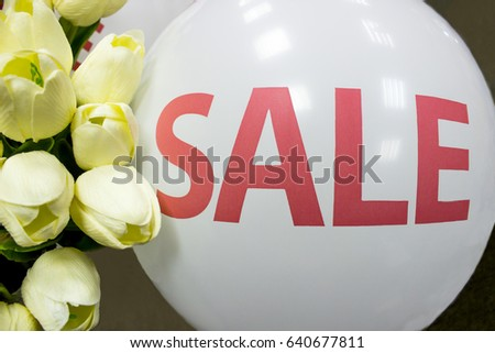 The white ball with the inscription sale near flowers. The white ball with the inscription sale. #640677811