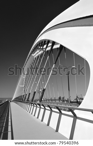The white bridge of a modern design against the sky. Monochrome