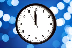 The white clock shows five seconds to midnight, with a bokeh background. Countdown to the New year