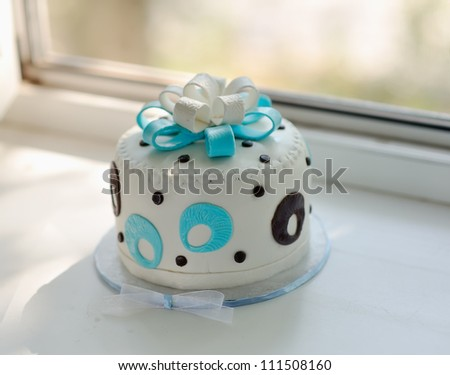 the white cream pie is decorated with a blue bow and drawing