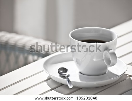 The white Cup of coffee on a white wooden Desk - stock photo