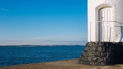 The white door of the lighthouse against the background of the sea coast.