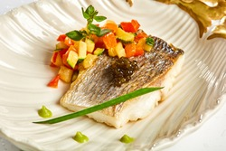 The white fish on plate with vegetables and decorated black caviar. Kosher food. Shallow dof