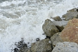 The white foam from the sea water splashed against the big rocks by the sea, shattering into tiny sprays.
