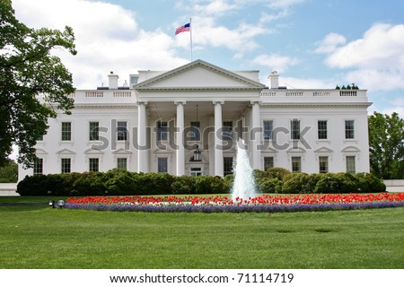 The White House in Washington DC in spring with fountain and red tulips.
