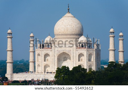 The white marble of the entire full front facade of Taj Mahal is seen from a telephoto distance shining brilliantly during a blue sky day in Agra, India. Horizontal copy space