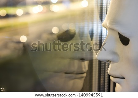 The white mask is reflected in the window. Night lights bokeh. Loneliness concept. #1409945591