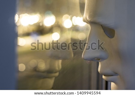 The white mask is reflected in the window. Night lights bokeh. Loneliness concept. #1409945594