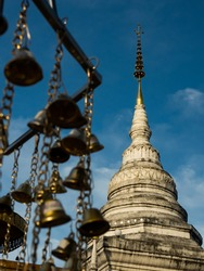 The white pagoda of Buddha's relics at Wat Phra That Kao Noi (Phra That Khao Noi Temple) with the small bells in foreground that visitors worship the relics.