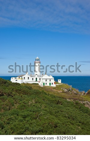 The white painted lighthouse at Fanad Head, Donegal, Ireland stands on a cliff top above the blue Atlantic Ocean, a safety beacon for shipping in the dangerous coastal waters around the rocky shores.