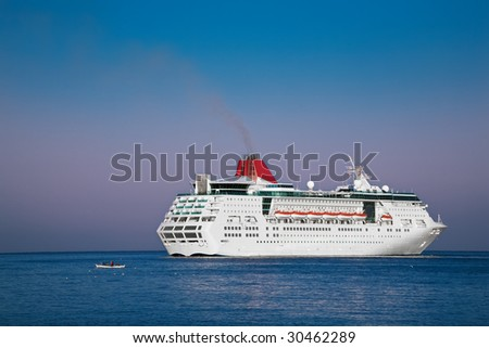 The white passenger steam-ship going by a small fishing boat across Aegean sea
