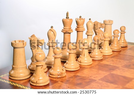 The white pieces set up on a chessboard. The focus runs diagonally along the main pieces on the back rank (tilt-shift lens effect).
