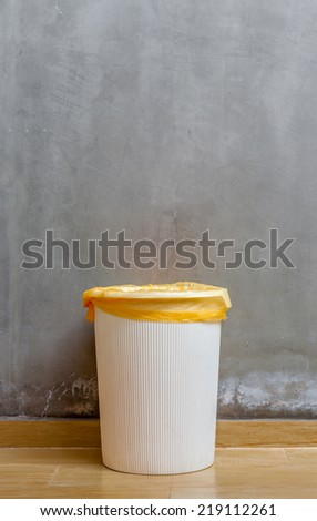 The white plastic bin with orange bag on wooden floor with exposed cement background, for cleaning and recycle. #219112261