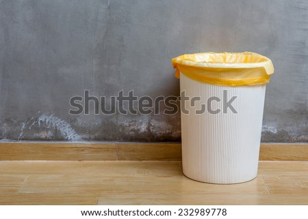 The white plastic bin with orange bag on wooden floor with exposed cement background, for cleaning and recycle. #232989778