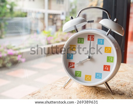 The  white retro alarm clock with colorful number is showing 8 o\'clock on wooden background and window glass