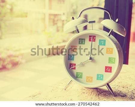 The  white retro alarm clock with colorful number is showing 8 o\'clock on wooden background and window glass in vintage style.