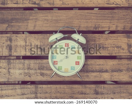 The  white retro alarm clock with colorful number is showing 8 o\'clock on wooden background in vintage style.