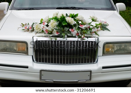 The white wedding car decorated with flowers