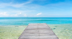 The white wooden bridge stretches out into the calm sea.