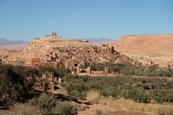 The whole UNESCO World Heritage Site of Ait Beb Haddou seen from the village on the other side of the river. The mud brick fortified town known as a kasbah is shown in beautiful late afternoon light