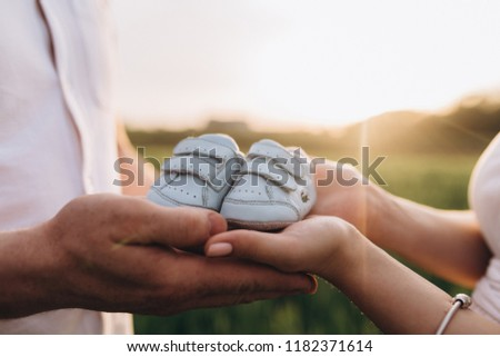 The wife and husband  keeping babyish shoes and standing on the field