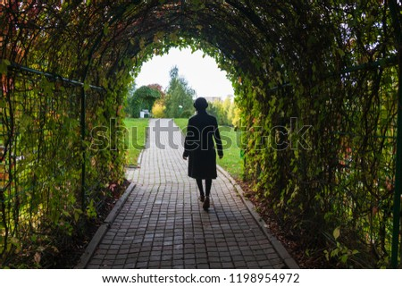 Stock Photo The wife is gone. A woman leaves through a tunnel of wild grape leaves