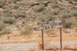 The Wild West. Western old city in Phoenix, Arizona, USA. Gold rush city. Old Arizona. A 'Stay on Trail Watch for snakes' sign in the desert. Wooden sign with an inscription.