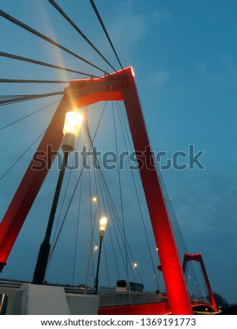 The Willems bridge and street lanterns by night in the Rotterdam. Red metal reliances on the blue sky background by the twilight.