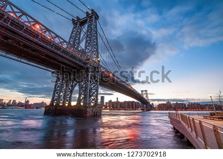 The Williamsburg Bridge is a suspension bridge across the East River at night in New York City , USA