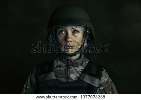 The willingness and courage. Close up portrait of young female soldier. Woman in military uniform on the war. Depressed and having problems with mental health and emotions, PTSD.