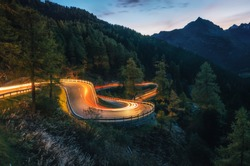 The winding mountain road with light tracks from cars at the evening, Maloja Pass, Switzerland
