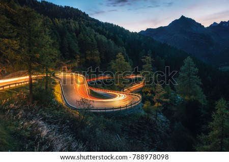 The winding mountain road with light tracks from cars at the evening, Maloja Pass, Switzerland #788978098