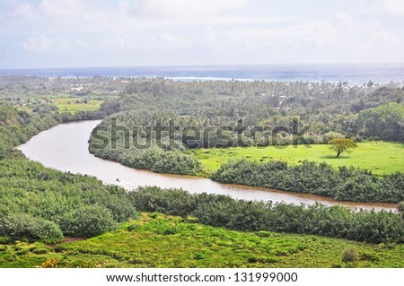 The winding Waimea River flows past lush fields into the Pacific, Kauai, HI