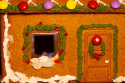 The window and door of the gingerbread house are decorated with multicolored glaze. The roof is decorated with candy. Taken in close-up.