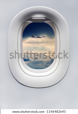 The window of the airplane with another passenger plane flying over the clouds side by side. A view from the porthole window on board an airbus for your travel concept or passenger air transportation.