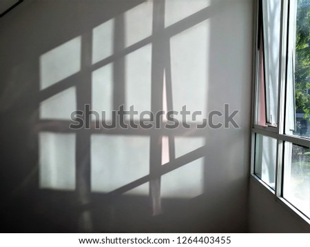 The window shade on the white wall.  #1264403455