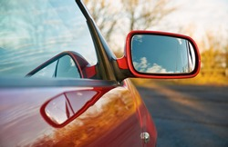 The wing mirror of a red car at sunset.