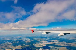 The wing of an airplane flying against the sky over the city. Travel concept.