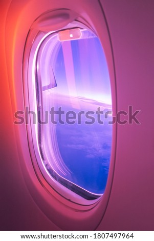 The wing of the plane and the sky, the stunning sunset in purple and red colors, the view from the window of the plane during the flight