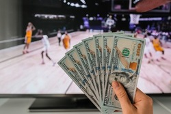 The winner at basketball betting holds a dollar money prize in hand near the TV